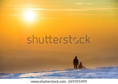 People looking at sunset in winter mountains covered with snow