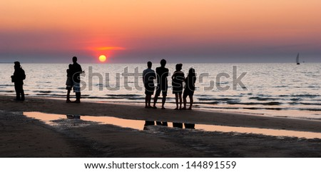 People looking at the sunset on a beach