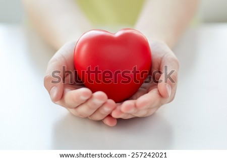 people, love, charity and family concept - close up of child hands holding red heart shape at home - stock photo