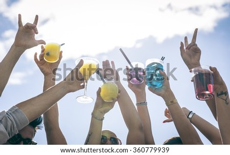 People making party and dancing on a beach party. Holding cocktails and pointing to the sky. - stock photo