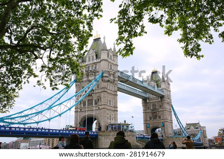 People making photos of beautiful Tower Bridge and River Thames on a sunny summer day, London, UK. Happy tourists enjoying view during travel to England.