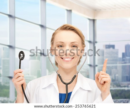 people, medicine and gesture concept - happy female doctor with stethoscope pointing her finger up over clinic background - stock photo