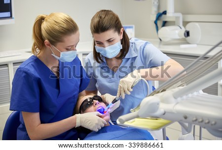 people, medicine, stomatology and health care concept - female dentists with dental curing light and mirror treating patient girl teeth at dental clinic office - stock photo