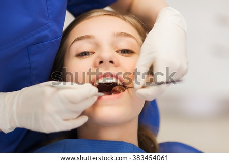 people, medicine, stomatology and health care concept - happy female dentist with mirror checking patient girl teeth up at dental clinic office - stock photo