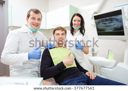 people, medicine, stomatology and health care concept - happy male dentist with assistant girl and patient at dental clinic office. Show thumbs up