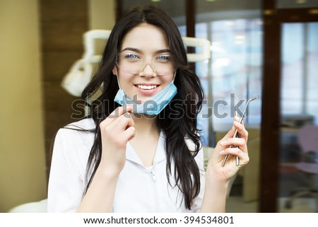 people, medicine, stomatology and healthcare concept - happy young female dentist with tools over medical office background. Dentist