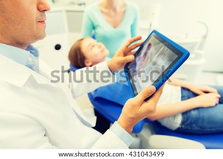 people, medicine, stomatology, technology and health care concept - close up of male dentist with x-ray on tablet pc computer screen and patient girl with her mother at dental clinic office - stock photo