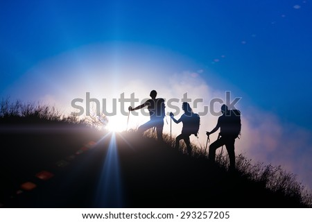 People meeting sunrise team building session. Group of people silhouettes walking toward mountain summit with backpacks hiking trekking gear meeting uprising sun sunbeams and blue sky of background - stock photo