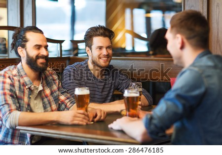 people, men, leisure, friendship and communication concept - happy male friends drinking beer at bar or pub - stock photo