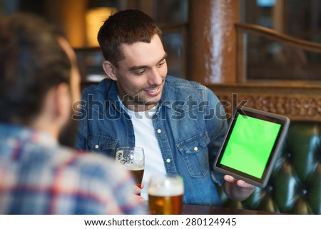 people, men, leisure, friendship and technology concept - happy male friends with tablet pc computer drinking beer at bar or pub