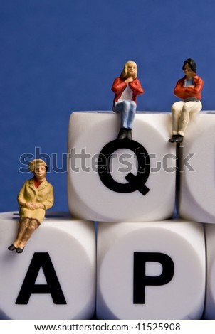 people miniature sitting on dices with alphabet letters - stock photo
