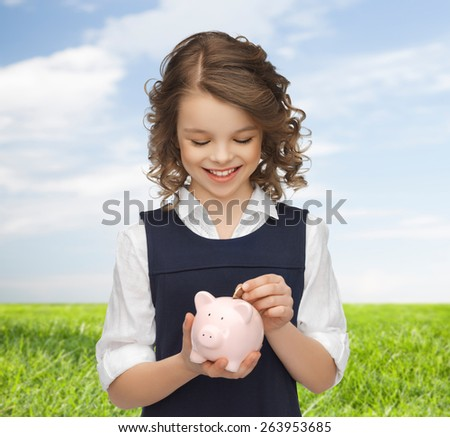 people, money, finances and savings concept - happy girl holding piggy bank and putting coin over blue sky and grass background - stock photo