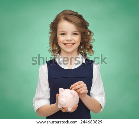 people, money, savings, investments and children concept - smiling school girl putting coin into piggy bank over green chalk board lights background - stock photo