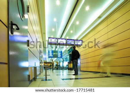 People mooving in hall corridor with tv displays in airport - stock photo