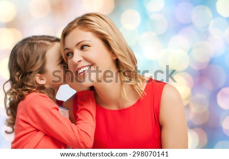people, motherhood, family and adoption concept - happy mother and daughter whispering something into ear over blue holidays lights background - stock photo