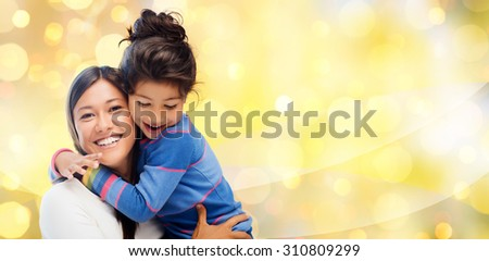 people, motherhood, family, holidays and adoption concept - happy mother and daughter hugging over yellow lights background - stock photo