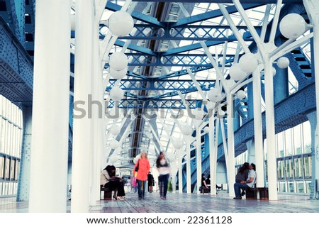People moving in a footbridge. Motion blue. Cross-process - stock photo