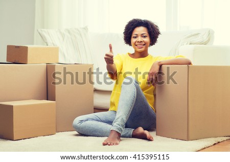 people, moving new place, gesture and repair concept - happy african american young woman with many cardboard boxes sitting on floor and showing thumbs up at home - stock photo