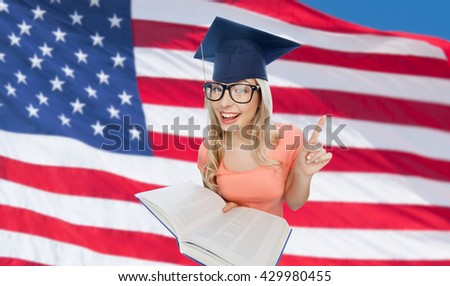 people, national education, knowledge and graduation concept - smiling young student woman in mortarboard and eyeglasses with encyclopedia book over american flag background