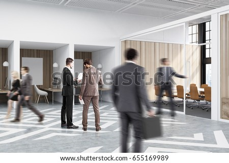 people near office cubicles in an office with white and wooden walls there are blank