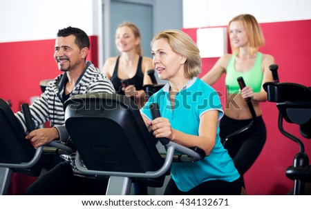 People of different age training on exercise bikes together