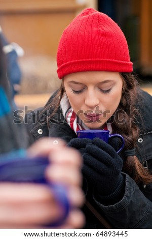 People on a Christmas market drinking punch or hot spiced wine, it is cold and they have a need to warm up - stock photo