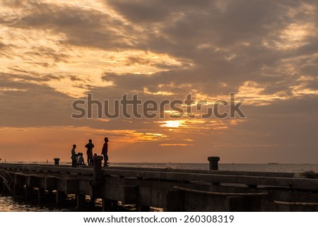 People on concrete jetty in the sunrise - stock photo
