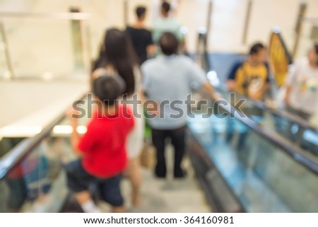 People  on escalator motion blurred. shopping abstract. - stock photo