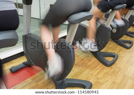People on exercise bikes in gym with wheels turning