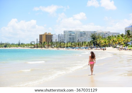 People on Isla Verde resort beach in Puerto Rico. Unrecognizable woman walking down the beach on summer holiday in bikini on famous Hispanic travel destination. - stock photo