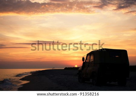 people on the beach at sunset time, parked car - stock photo