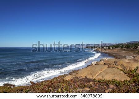 People on the beach, blue sky and sea, waves crashing at sunrise on Moonstone Beach next to Shamel Park and Santa Rosa Estuary, along Big Sur Coast, California Central Coast, near Cambria CA. - stock photo