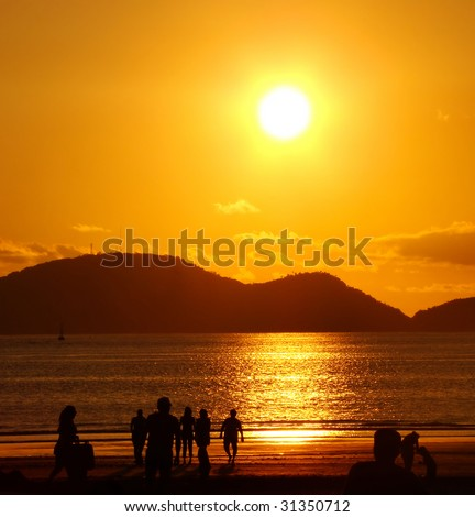 people on the beach under a beautiful golden sunset