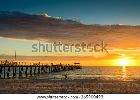 People on the beach walking on the jetty and young girl is doing fitness at sunset - stock photo