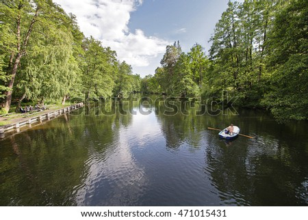 People on the boat floating in the pond of a country park