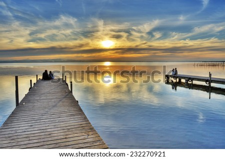 people on the docks watching the sunset - stock photo