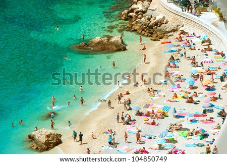 people on the sea beach with sunbeds and umbrellas. hot sunny summer day - stock photo