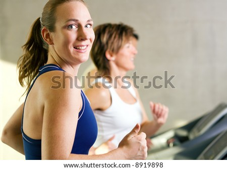 People on the treadmill, the girl in front smiling