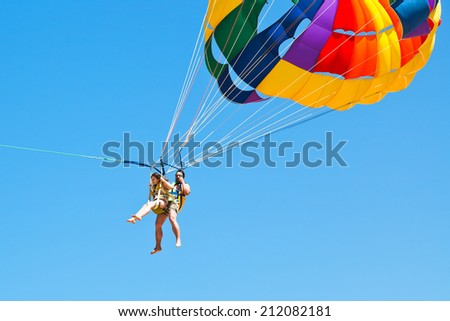 people parakiting on parachute in blue sky in summer day - stock photo