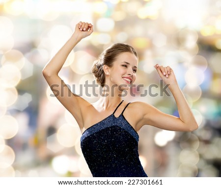 people, party, holidays and glamour concept - smiling woman dancing with raised hands over lights background - stock photo
