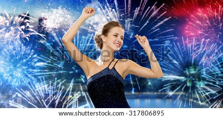 people, party, holidays and glamour concept - smiling woman dancing with raised hands over nigh city and firework background - stock photo