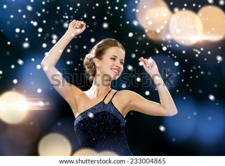 people, party, holidays and glamour concept - smiling woman dancing with raised hands over night lights background - stock photo