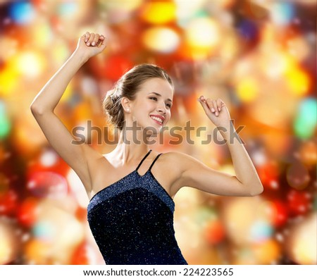 people, party, holidays and glamour concept - smiling woman dancing with raised hands over red lights background - stock photo