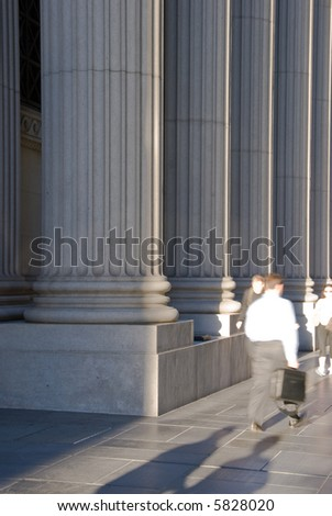 People passing by a bank in front of the ionic columns. Can also be a courthouse, university, etc. - stock photo