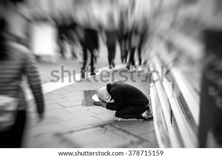 People passing indifferently next to beggar in the street of the modern city - stock photo