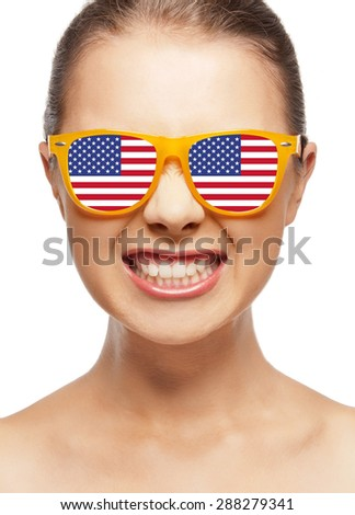 people, patriotism, national pride and independence day concept - funny teenage girl in sunglasses with american flag - stock photo