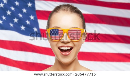 people, patriotism, national pride and independence day concept - happy teenage girl in sunglasses with american flag - stock photo
