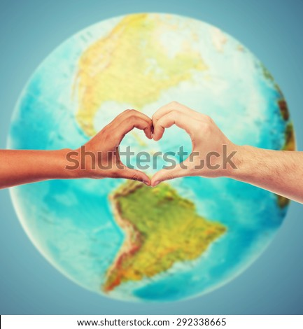 people, peace, love, life and environmental concept - close up of human hands showing heart shape gesture over earth globe and blue background - stock photo