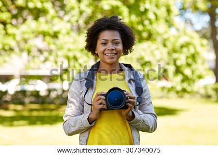 people, photography, technology, leisure and lifestyle - happy young african american female photographer with digital camera in summer park - stock photo