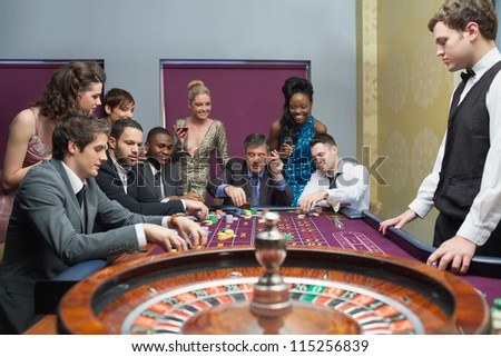 People placing bets on roulette table in casino - stock photo